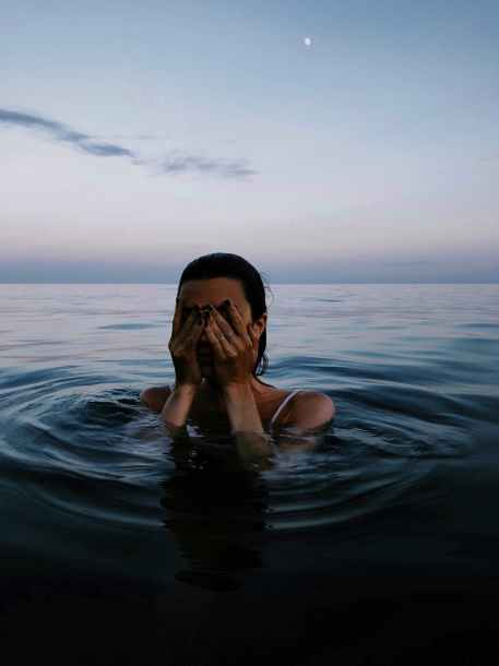 woman in water clearing his face of water